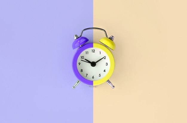 Ein kleiner wecker befindet sich zwischen den bereichen violett und creme