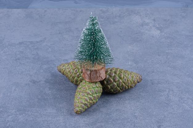 Ein kleiner weihnachtsbaum mit tannenzapfen auf einer grauen oberfläche
