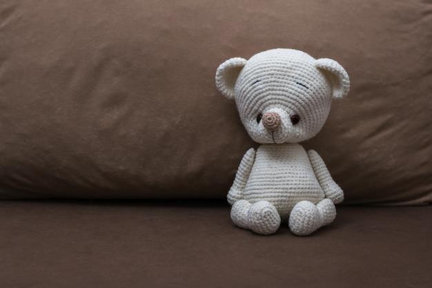 Ein kleiner weißer strickbär auf einem weichen sofa. schönes strickspielzeug.