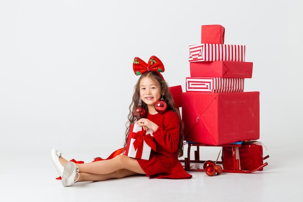 Ein kleines asiatisches mädchen, das in einem roten kleid sitzt, sitzt mit geschenkboxen auf einem weißen hintergrund. weihnachtskonzept, textraum
