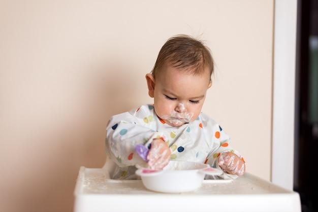 Ein kleines baby, das ihr abendessen isst und ein durcheinander macht