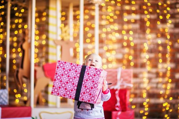 Ein kleines blondes mädchen im weihnachtspyjama hält ein geschenk. foto in hoher qualität