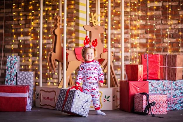 Ein kleines blondes mädchen im weihnachtspyjama hält ein geschenk vor dem hintergrund des karussells. foto in hoher qualität