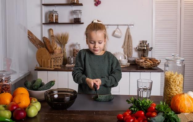 Ein kleines blondes mädchen in einem grünen pullover sitzt an einem tisch und schneidet eine gurke