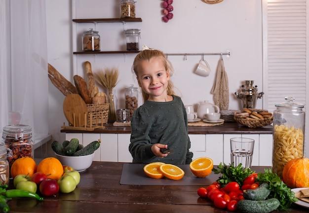 Ein kleines blondes mädchen in einem grünen pullover sitzt an einem tisch und schneidet eine orange