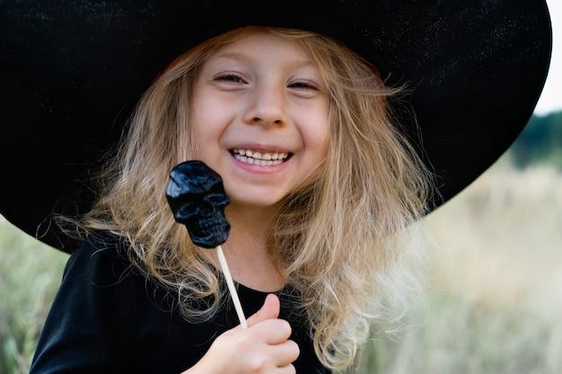 Ein kleines blondes mädchen in einem schwarzen kostüm und einem hexenhut, halloween mit einem süßigkeitenschädel in den händen, ein fröhliches kind, nahaufnahme