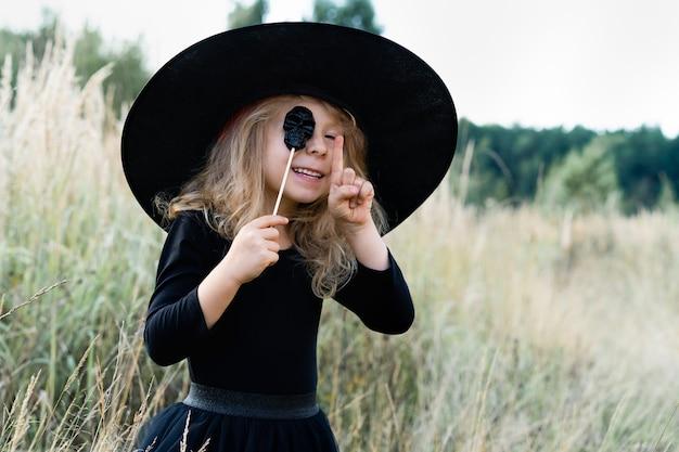 Ein kleines blondes mädchen in schwarzem kostüm und hexenhut, halloween mit einem süßigkeitenschädel in den händen, ein fröhliches kind.