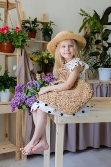 Ein kleines blondes mädchen mit einem strauß lila blumen sitzt auf einem holzstuhl im zimmer