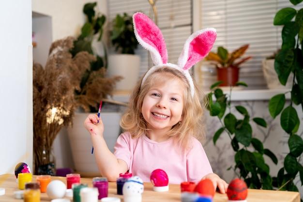 Ein kleines blondes mädchen sitzt am tisch und malt ostereier mit pinseln und malt ein lächeln