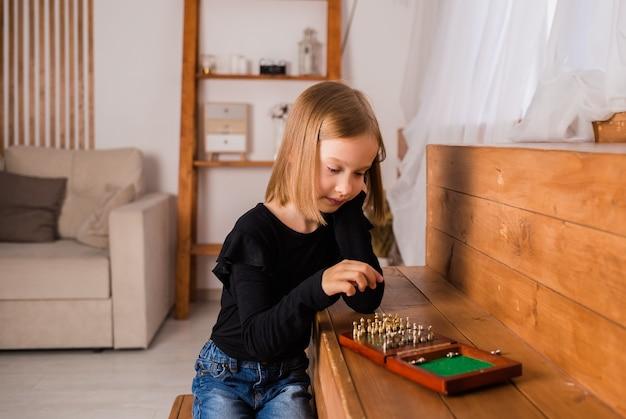 Ein kleines blondes mädchen spielt schach im zimmer. intellektuelles spiel
