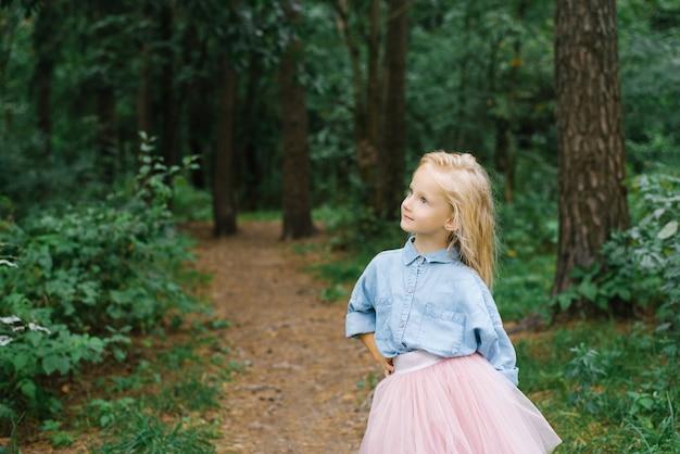 Ein kleines blondes mädchen von fünf jahren in romantischen kleidern denkt an etwas im wald oder im park
