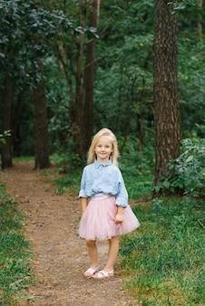 Ein kleines blondes mädchen von fünf jahren in romantischer kleidung geht einen waldweg entlang und lächelt