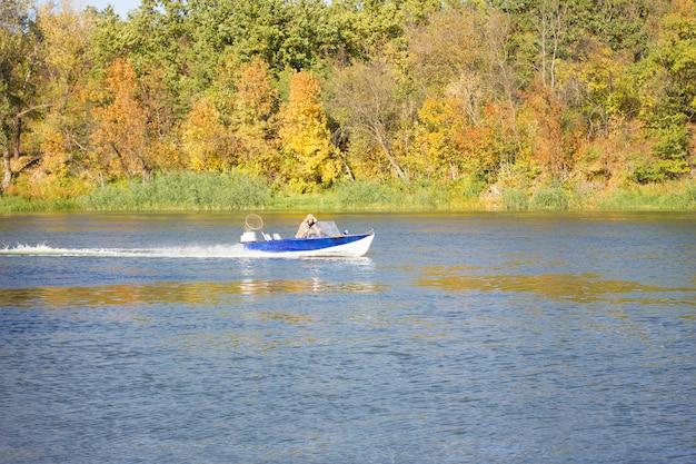 Ein kleines boot schwimmt auf dem herbstfluß. fischer segeln auf einem boot