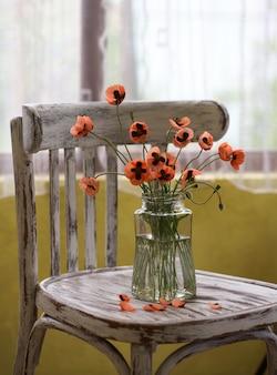 Ein kleines bouquet aus roten mohnblumen im klassischen stil stillife von popies in einer brillenvase auf einem vintage-stuhl