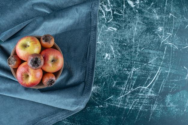 Ein kleines bündel mispelfrüchte und äpfel in der schüssel, auf dem handtuch, auf dem blauen hintergrund. hochwertiges foto
