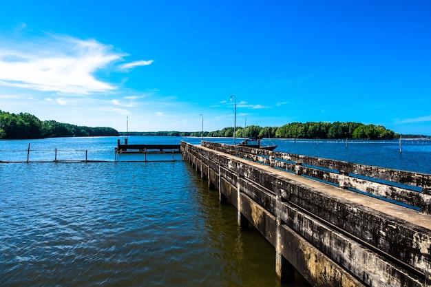 Ein kleines dock oder ein plankensteg über dem meer auf hintergrund des mangrovenwaldes und des blauen himmels.