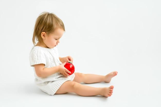 Ein kleines einjähriges mädchen spielt mit einer gläsernen roten weihnachtskugel