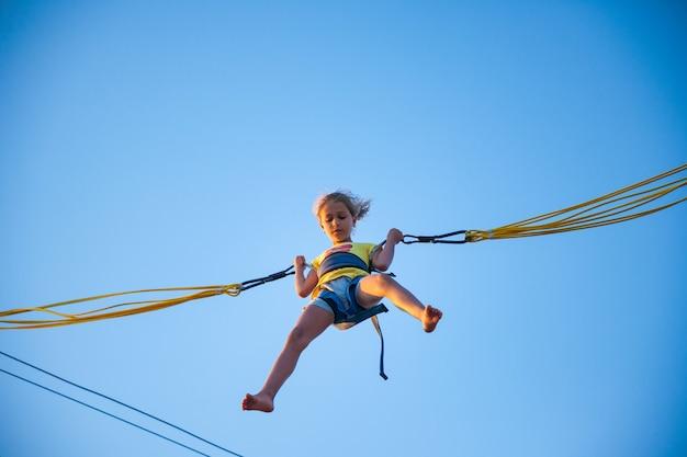 Ein kleines fröhliches mädchen fliegt auf federnden hellen gummibändern und springt auf ein trampolin, um den lang erwarteten urlaub in der warmen sonne zu genießen