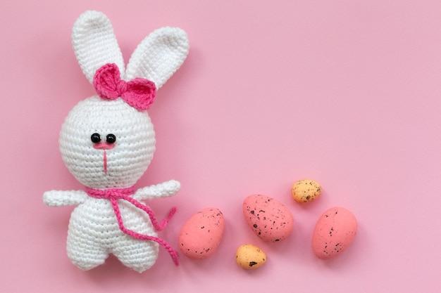 Ein kleines gestricktes babyspielzeug-kaninchen mit ostereiern auf rosa hintergrund. flache lage, draufsicht. osterkonzept.