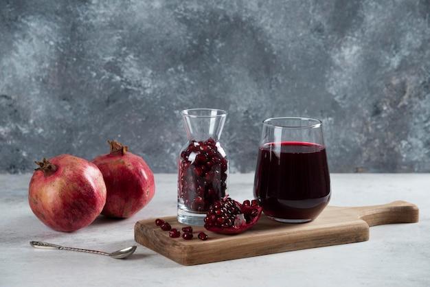 Ein kleines glas voller granatapfel und eine tasse saft.