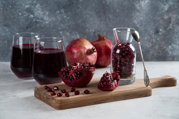 Ein kleines glas voller granatapfel und tassen saft.