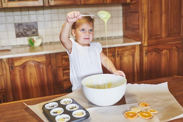 Ein kleines gutes mädchen backt leckere cupcakes