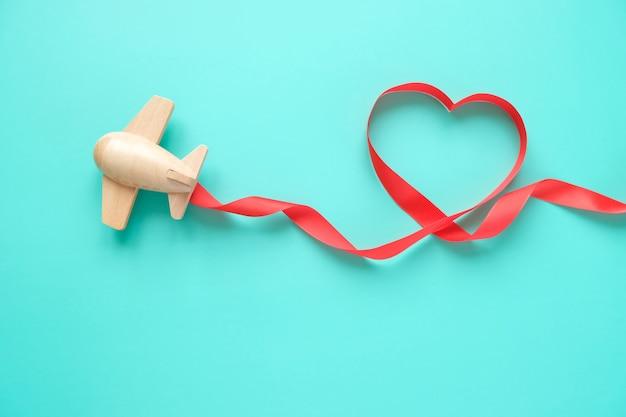 Ein kleines hölzernes spielzeugflugzeug trägt valentinselemente. kondensstreifen aus pailletten in form eines herzens und rotem band in form eines herzens. valentinstag