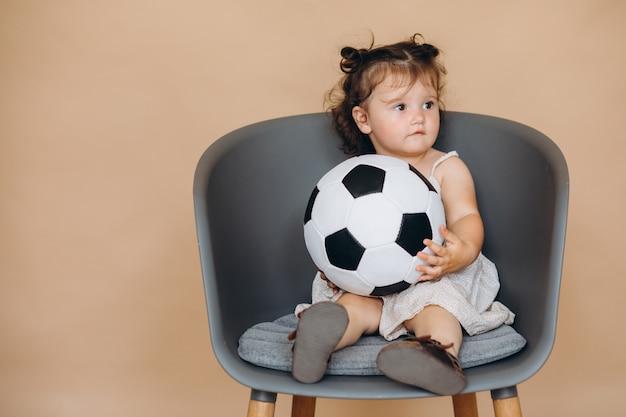 Ein kleines hübsches mädchen hält den ball und schaut fußball und beifall für ihre mannschaft