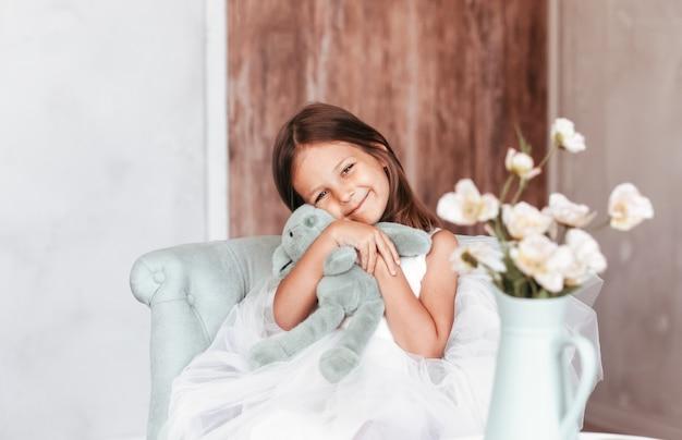 Ein kleines hübsches mädchen sitzt auf einem stuhl und umarmt ein stofftier. glückliche kindheit