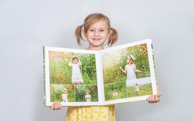Ein kleines kaukasisches mädchen, das ein fotobuch mit ihren fotografien in ihren händen hält