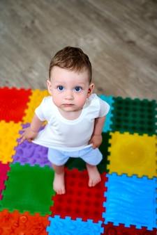 Ein kleines kind auf einer orthopädischen matte barfuß.