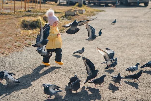 Ein kleines kind, das tauben jagt. mädchen füttern vögel. konzept der kindheit, straßenspiele
