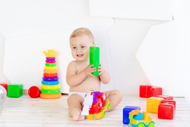 Ein kleines kind, ein junge spielt mit hellen spielsachen in einem hellen weißen raum in windeln