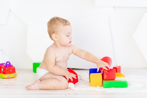 Ein kleines kind, ein junge spielt mit hellen würfeln in einem hellen weißen raum in windeln