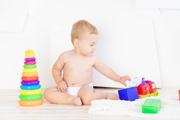 Ein kleines kind, ein junge von sechs monaten, spielt mit hellen würfeln und einer pyramide in einem hellen weißen raum in windeln