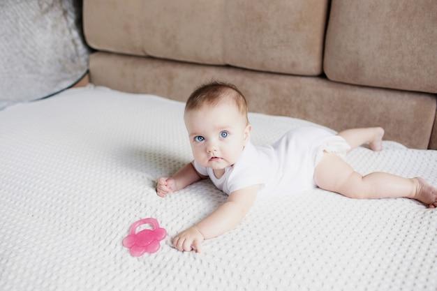 Ein kleines kind, ein mädchen mit blauen augen, kriecht auf dem bett