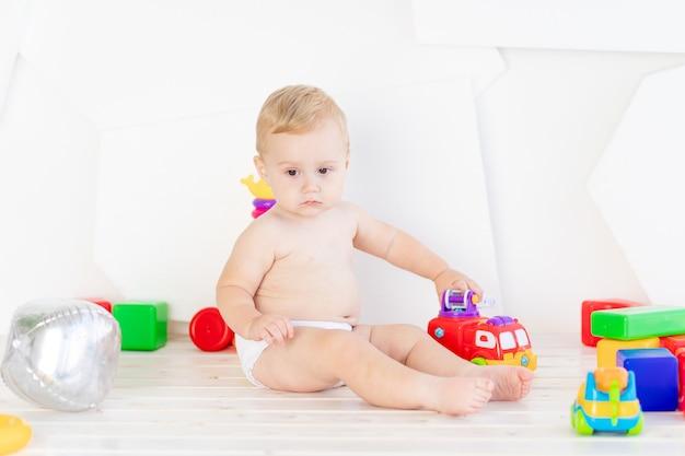 Ein kleines kind, ein sechs monate alter junge, spielt mit hellen spielsachen in einem hellen weißen raum in windeln