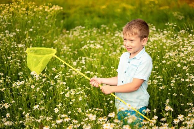 Ein kleines kind geht durch ein gänseblümchenfeld, hält ein netz in der hand und fängt schmetterlinge