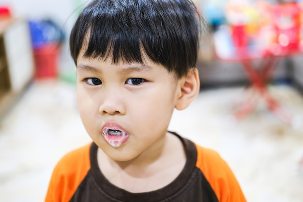 Ein kleines kind genießt den speichelschaum, der aus seinem mund spuckt.