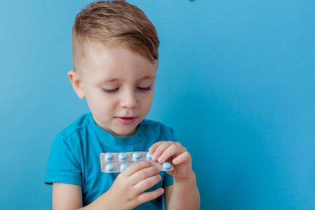 Ein kleines kind hält in seiner handfläche eine handvoll pillen auf blauem hintergrund.