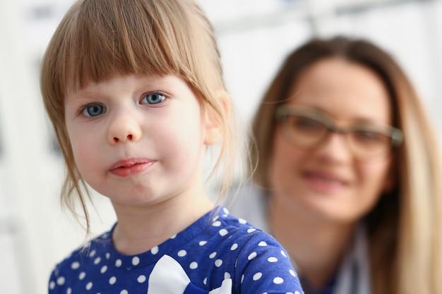 Ein kleines kind hat angst im krankenzimmer. der arzt hält seine hände und beruhigt das porträt.