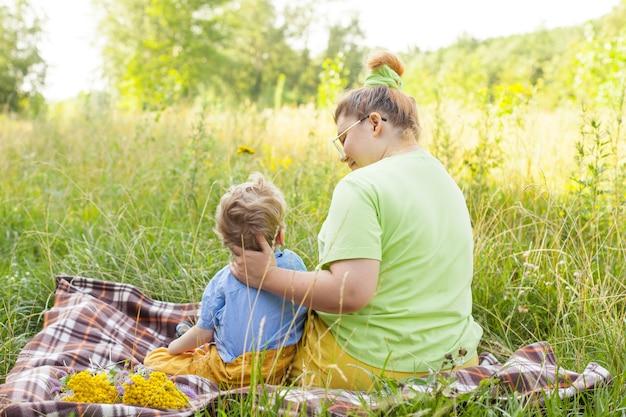 Ein kleines kind im rollstuhl spielt mit seiner mutter an der frischen luft. leben im bildungsalter behinderter kinder, das konzept eines glücklichen behinderten kindes.