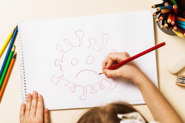 Ein kleines kind in der quarantäne zu hause zeichnet ein coronavirus