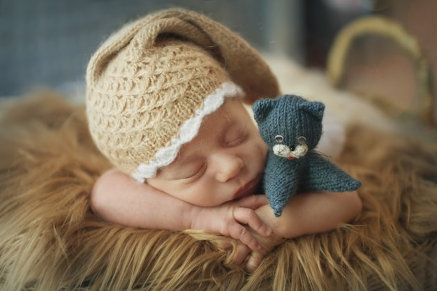 Ein kleines kind in einem korb schläft in einer warmen strickmütze mit pompon