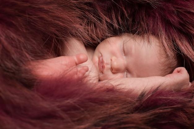 Ein kleines kind in einem roten pelz liegt. portrait des neugeborenen
