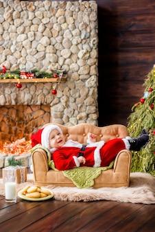 Ein kleines kind in einem roten weihnachtsmannkostüm liegt auf der couch in der residenz