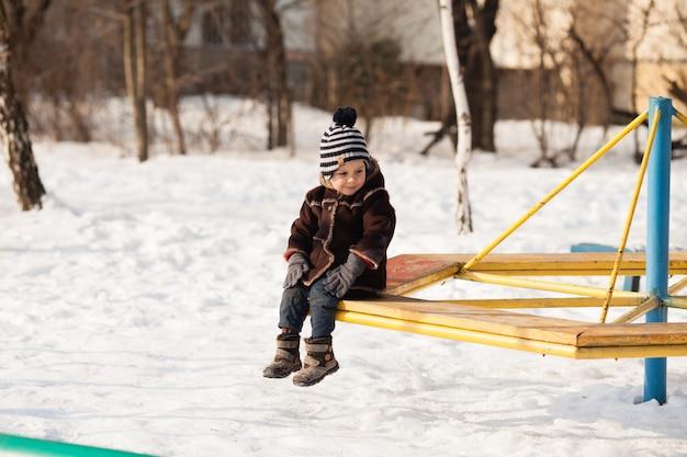 Ein kleines kind in einer warmen braunen jacke und mütze, das am wintertag auf dem spielplatz spielt