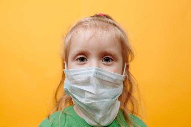 Ein kleines kind in einer weißen medizinischen maske an einer gelben wand. coronavirus. schutz der kinder vor der epidemie
