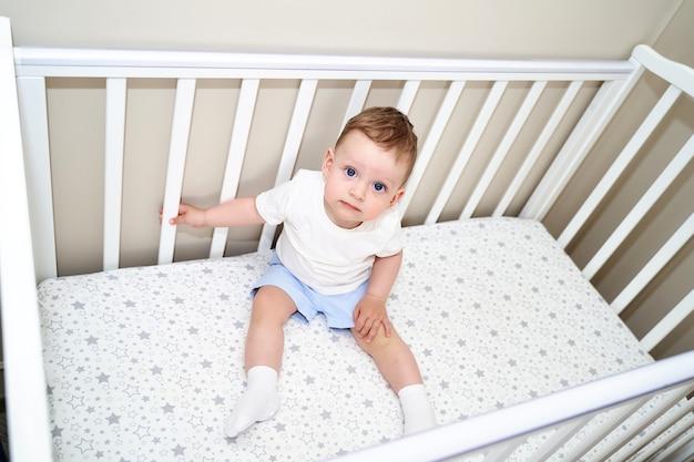 Ein kleines kind liegt in einem kinderbett. ansicht von oben.