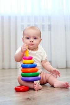 Ein kleines kind mit blauem kleinkind mit blauen augen spielt im spielzimmer. die augen spielen im spielzimmer